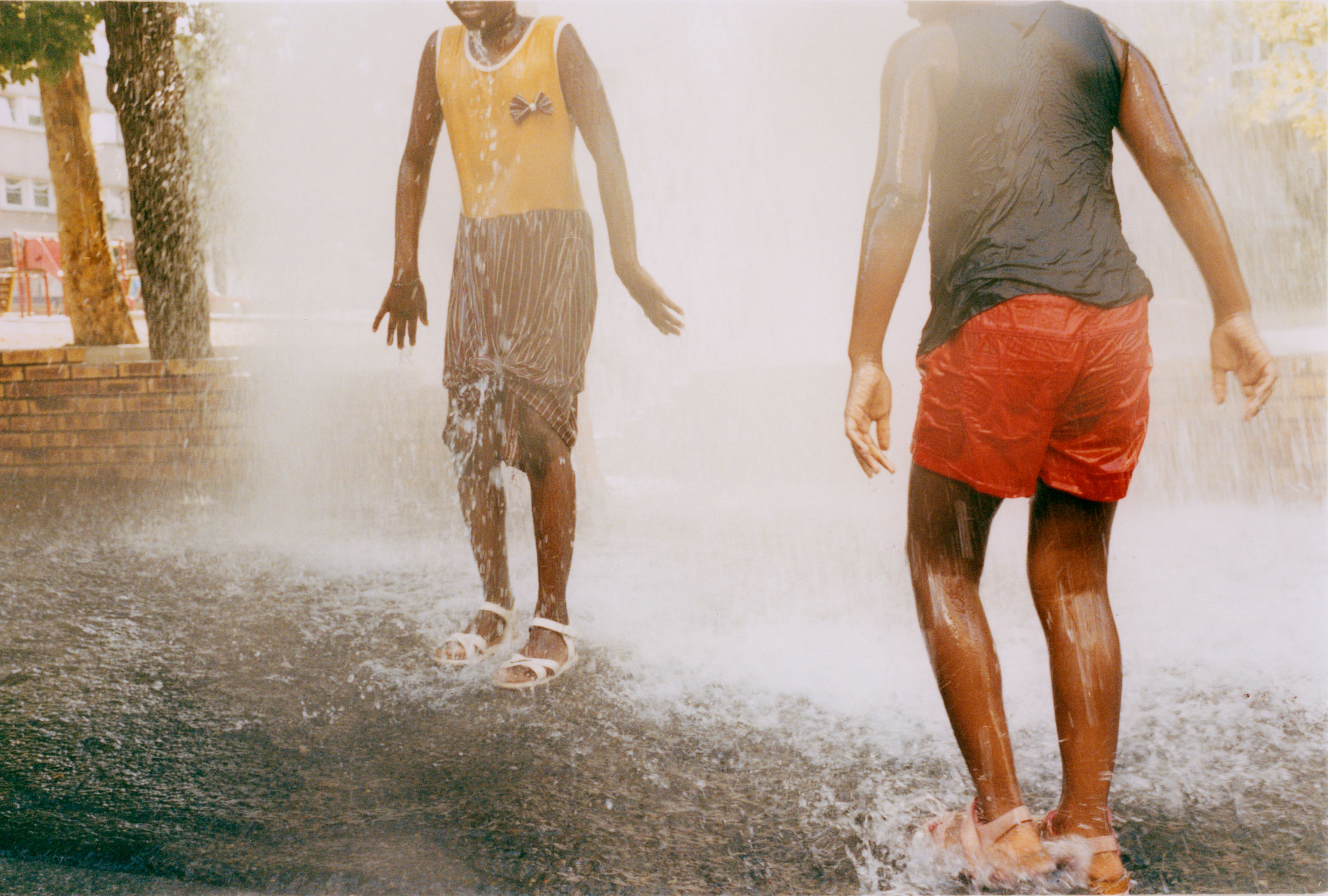 Kids keeping cool in my street during the heatwave. From my ongoing project *Paris Nord*, documenting my local neighbourhood in the suburb of Seine Saint Denis, which can be viewed in its entirety in the *Studies* section of this website. - © Maciek Pożoga